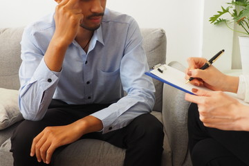 Asian man seeking advice from professional female psychiatrist to diagnose his mental disorder and emotion due to his stress about work and life problems. Psychological consultation and health concept