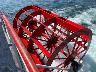 Red paddle wheel of a boat up close
