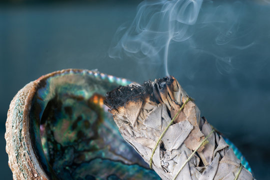 Smudging Ritual using burning thick leafy bundle of White Sage in bright polished Rainbow Abalone Shell on the beach at sunrise in front of the lake.