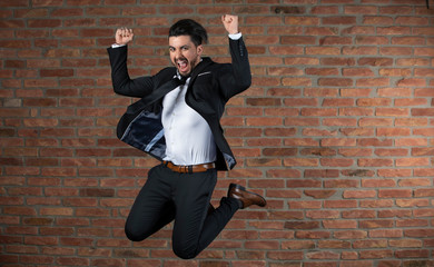 Handsome young businessman jumping in the air in a studio