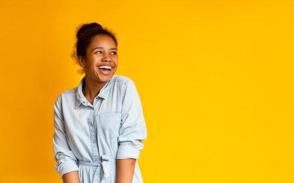 Excited black teen looking upwards standing against yellow studio background