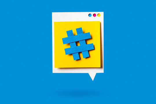 Paper cutout of hashtag symbol on a yellow speech bubble on blue background. Concept of social media and digital marketing.