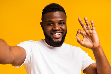 African man making selfie and showing ok sign at camera