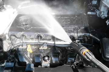 Car detailing. Manual car wash engine with pressure water. Washing car engine with water nozzle....