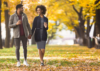 Happy african-american couple with coffee cups walking in park