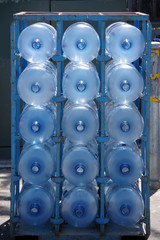 Close front view of a rack stacked with empty large water bottles