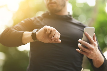 Man checking data on fitness tracker after training outdoors