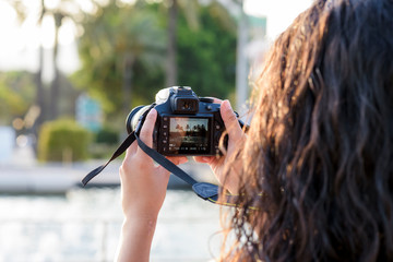 Portrait of young woman  making photos with a professional digital camera in a city.