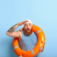 Emotional male lifeguard stares into distance, notices sinking person at sea, helps people to survive, carries inflated lifebuoy, stares with bugged eyes, wears rubber swimming cap, isolated on blue