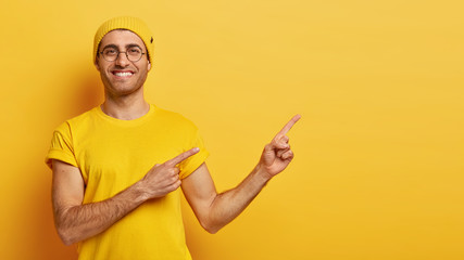 Pick best choice. Glad smiling man points aside on right side, shows blank copy space, advertises cool object, recommends product, wears vivid yellow attire, stands indoor, attracts your attention
