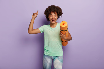 Glad dark skinned woman attends fitness class, holds rolled up mat, dressed in sportswear, points up, has athletic body and exercises in gym happy after workout or cardio training. Sport and lifestyle