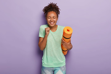 Bodycare and sport concept. Energized glad dark skinned woman clenches fist with joy, holds fitness...