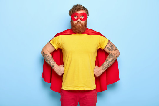 Photo of serious male in superhero costume, keeps hands on waist, possesses extraordinary talents, ready to protect our universe, isolated on blue wall. Bearded guy in red mask, cape, yellow t shirt