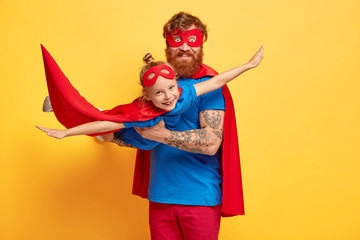 Happy dad and daughter play superhero game, bearded father holds small child on hands, imitate flight, pretend being real superheroes, dressed in capes and masks. Strong family and entertainment Fototapete