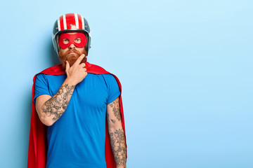 People and super power concept. Serious man with red thick beard, wears helmet and red superhero cape, has tattooed arm, looks confidently at camera, stands against blue wall, copy space area on right