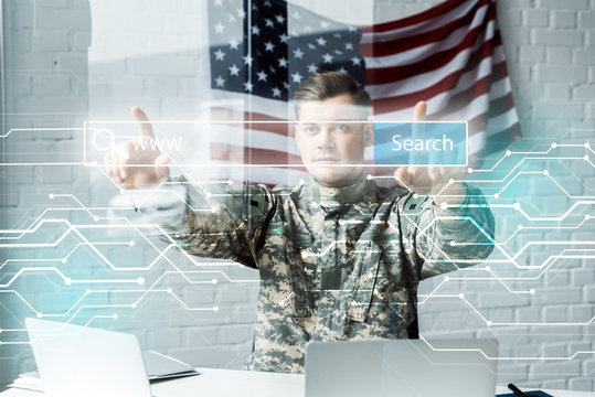man in military uniform pointing with fingers at address bar in office