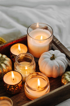 Burning candles pumpkin decoration on wooden tray with warm plaid in bed. Autumn style. Hygge concept.