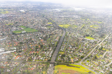 Auckland city aerial, suburban and industrial areas below.