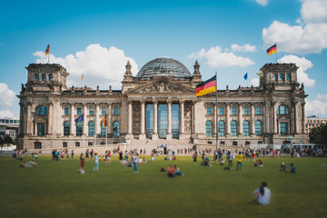 Many people on meadow in front of the Reichstag building (German Bundestag), a famous  landmark on a sunny, summer day Wall mural