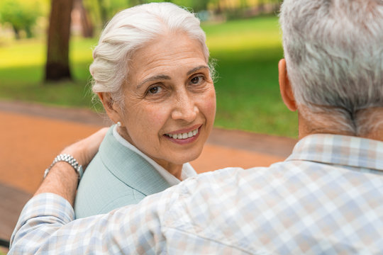 Smiling old woman with look at camera at park with her husband with view from back
