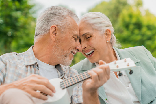 Close up shot of senior man playing on ukulele to his wife on a picnic and bonding to each other