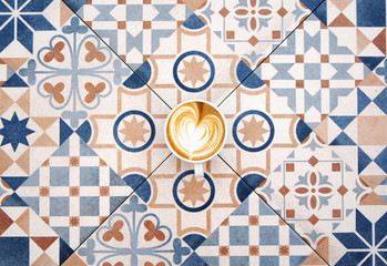 Cup of coffee on colorful tile background. Cup of coffee top view