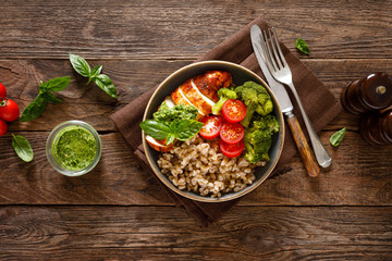 Chicken lunch bowl with broccoli, fresh tomato, pearl barley porridge and basil pesto on wooden...