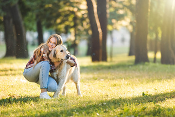 Wall Mural - full length view of beautiful young girl in casual clothes hugging golden retriever while sitting on meadow in sunlight and looking at camera