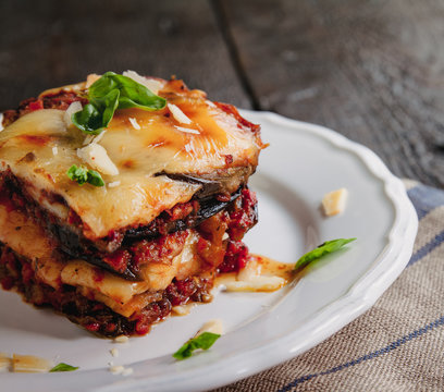 tradicional Parmigiana di melanzane: baked eggplant - italy, sicily cousine.Baked eggplant with cheese, tomatoes and spices on a white plate. A dish of eggplant is on a wooden table