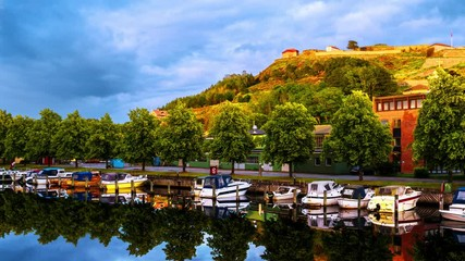 Wall Mural - Halden, Norway. View of the boats and yachts with Fredriksted fortress at the background. Time-lapse in the evening with cloudy sky in summer, panning video