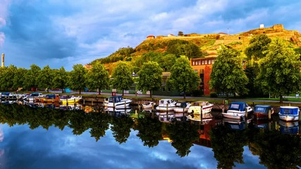 Wall Mural - Halden, Norway. View of the boats and yachts with Fredriksted fortress at the background. Time-lapse in the evening with cloudy sky in summer, zoom in