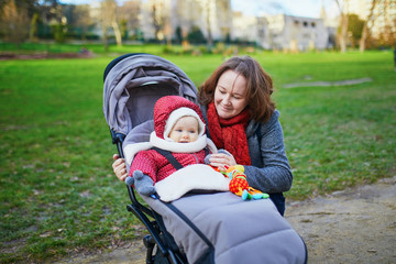 woman with her little baby girl in stroller. Mother walking in park