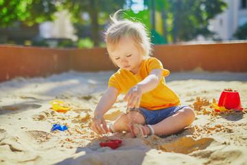 little girl having fun on playground in sandpit