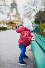 Baby girl standing on the street and holding on to bench