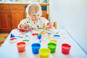 little girl painting with fingers at home