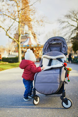 Baby girl standing on the street and holding on to pushchair