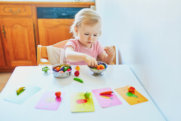 Adorable little girl playing with toy fruits and vegetables