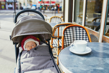Baby girl sleeping in pram on outdoor terrace of Parisian street cafe
