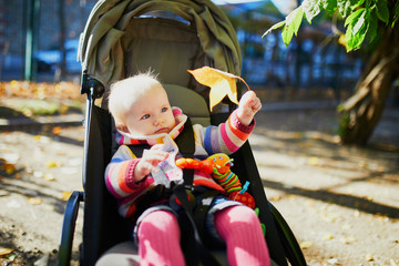 girl in bright stylish clothes sitting in pushchair outdoors on a fall day