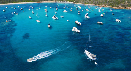 Wall Mural - View from above, stunning aerial view of a beautiful bay full of boats and luxury yachts. A turquoise sea bathes the green and rocky coasts. Liscia Ruja, Emerald Coast (Costa Smeralda) Sardinia, Italy