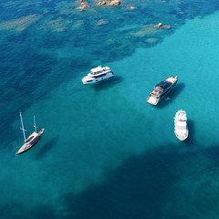 Wall Mural - View from above, stunning aerial view of a beautiful bay with turquoise water full of boats and luxury yachts. Liscia Ruja, Emerald Coast (Costa Smeralda) Sardinia, Italy.