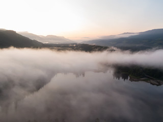 Aerial Panoramic View of Fairy Lake covered in clouds during a vibrant summer sunrise. Taken near Port Renfrew, Vancouver Island, British Columbia, Canada.