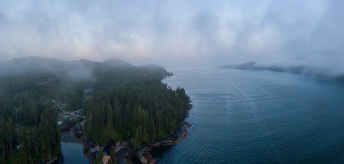 Aerial Panoramic View of a small secluded town on the Pacific Ocean Coast during a cloudy summer sunrise. Taken in Port Renfrew, Vancouver Island, BC, Canada.