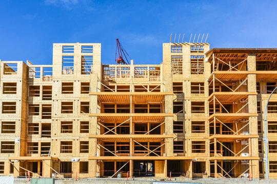 Six storey frame building under construction on concrete foundation bed.