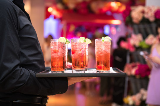 Refreshing alcohol red cocktails with ice and lemon on waiter plate on evening event party