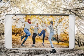 Positive happy women jumping in autumn forest, demonstration of device capabilities