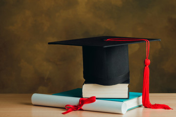 Graduation day,graduation cap,books and certificated on wooden.Graduation concept