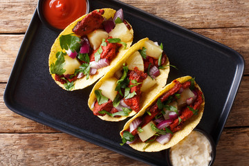Traditional Mexican tacos al pastor with pork, pineapple, onions and herbs close-up on a plate. horizontal top view