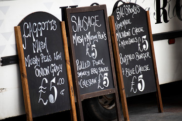 Menu and price boards propped up against mobile food trailer at weekly Saturday marketplace