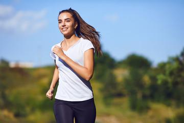 Girl runner runs along in nature in summer.
